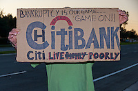 "A man holds a sign reading ""Citibank - Bankruptcy is our game … game on!! Citi. Live -Richly- Poorly"" at the Occupy Orange County - Irvine camp."