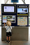 A young schoolboy plays with a touch-panel map device outside a station in Tokyo, Japan.