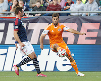 Houston Dynamo forward Will Bruin (12) dribbles down the wing.  In a Major League Soccer (MLS) match, the New England Revolution (blue/white) defeated Houston Dynamo (orange), 2-0, at Gillette Stadium on April 12, 2014.