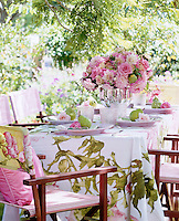 A pretty summer table under the trees with a floral tablecloth and director's chairs with co-ordinated fabric seats
