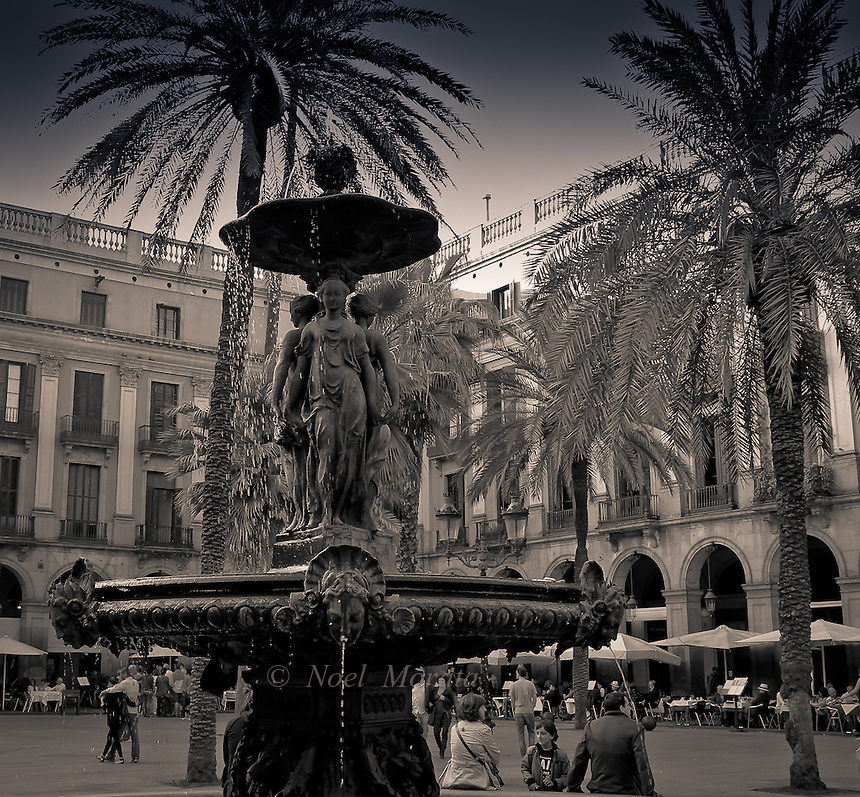 Placa Real in Barcelona Spain, a famous square lined with beautiful buildings, cafes, fountains and people watching