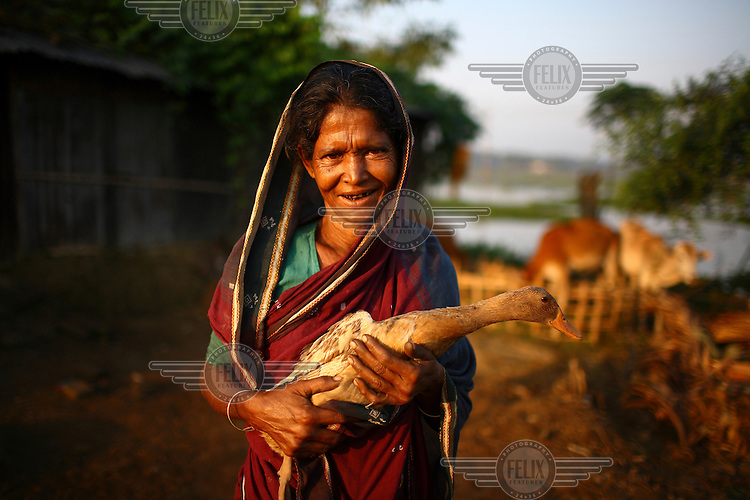 45 year old Amina Begum holds one of the ducks that she was able to buy with the help of a microfinance loan from IFAD (International Fund for Agricultural Development).