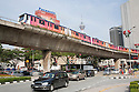 A road junction with a RapidKL train traveling on an elevated railway in downtown Kuala Lumpur, Malaysia.