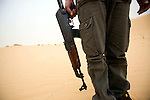 A Bedouin smuggler, armed with an AK-47 rifle, in the Sinai desert, not far from the border with Israel, Jan. 30, 2010. Some Bedouin make a living smuggling goods and humans from Egypt across the Gaza and Israel borders. A barrier wall being built buy Egypt may impact the illegal trade, causing strife between the government and Egypt's marginalized Bedouin tribes.