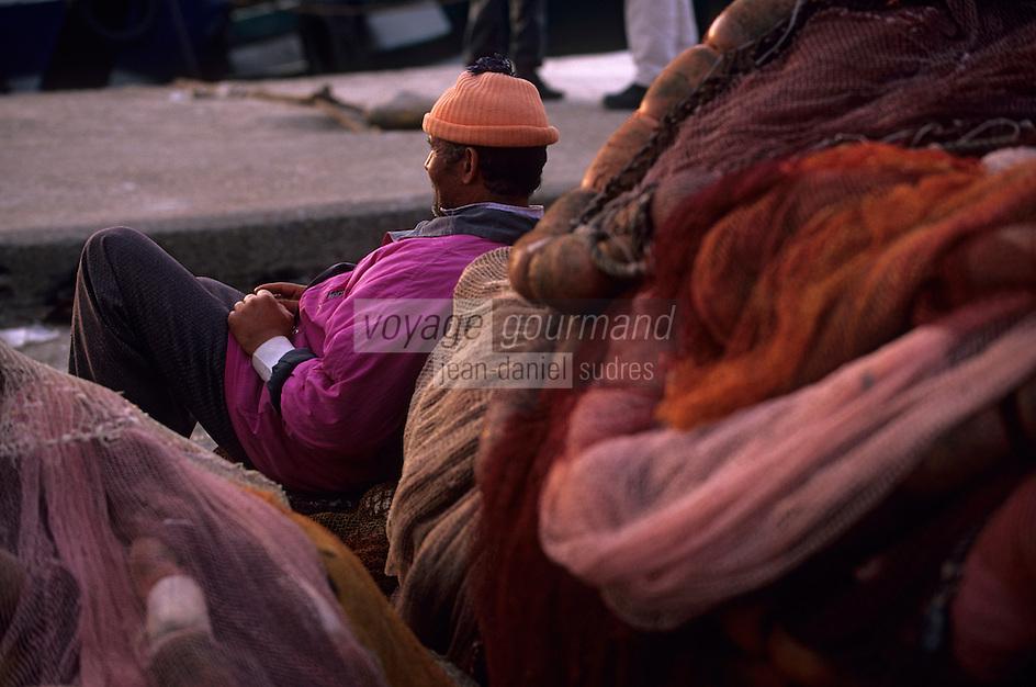 Afrique/Maghreb/Maroc/Essaouira : Le port de pêche, pêcheur se reposant parmi les filets de pêche