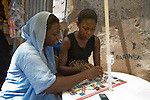 Two young women in the Garki area of Abuja, Nigeria play a board game designed by the Society for Family Health to educate out-of-school youth about HIV prevention.