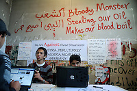 Local journalists discuss and update the Facebook page of the 17 February Movement, as the revolutionary movement is sometimes dubbed. Graffiti on the wall reads 'Bloody Monster stealing our oil, makes our blood boil.' On 17 February 2011 Libya saw the beginnings of a revolution against the 41 year regime of Col Muammar Gaddafi. ..