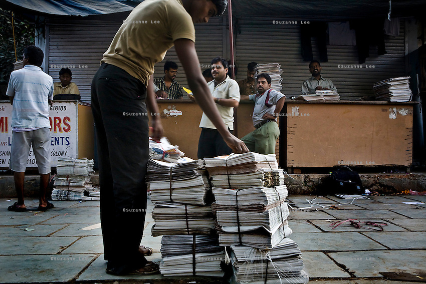 Newsstand owners buy in bulk from the newspaper distributors in the Mehar Chand market street early in the morning on 20th October 2008 in New Delhi, India. With internet still out of reach for 95% of the country and literacy higher than ever, more and more are turning to newspapers and magazines.  Photo : Suzanne Lee