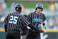 Danny Hayes (20) of the Charlotte Knights is congratulated by third base coach Garey Ingram (25) as he rounds the bases after hitting a home run against the Norfolk Tides at BB&T BallPark on May 2, 2017 in Charlotte, North Carolina.  The Knights defeated the Tides 8-3.  (Brian Westerholt/Four Seam Images)
