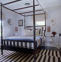 The master bedroom is decorated in bold stripes from the Turkish kilim on the floor to the blanket on the bed