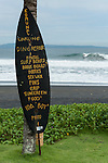 Komune Resort & Beach Club, Bali, Indonesia; a surf board displays services available near the beach while a surfer catches a wave in the background