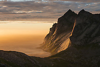 Evening sunlight shines across Helvetestind mountain peak and Bunes beach, Moskenesøy, Lofoten Islands, Norway