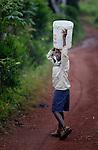 A boy carries water as he walks on a path through Mizak, a small village in the south of Haiti.
