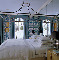 Doors dressed in Brunschwig & Fils fabric lead from the guest bedroom into a tented solarium