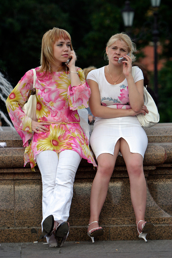 Moscow, Russia, 31/07/2004..Two girls speaking on mobile phone in Manezh Square by the Kremlin.