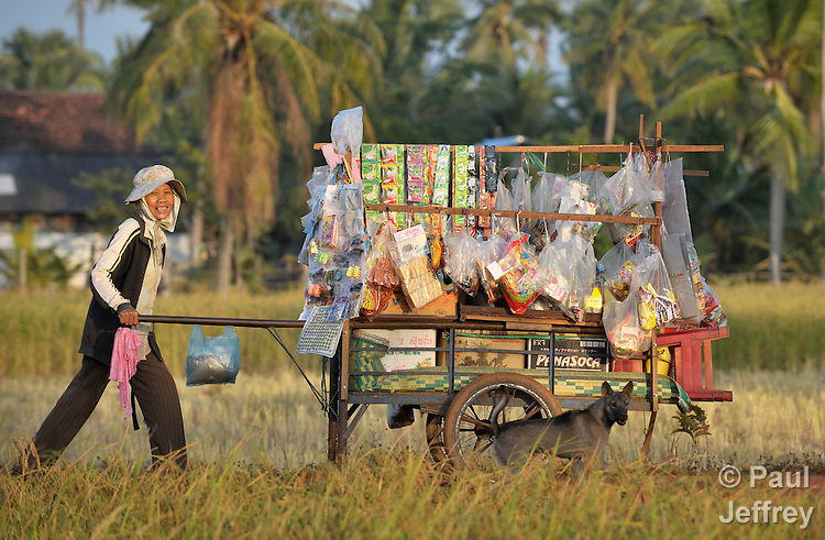 A woman pushes a wagon with her wares for sale through a rice field in Khnach, a village in the Kampot region of Cambodia.