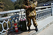A Chinese border policeman is seen standing with a fire extinguisher on the Friendship Bridge in Tatopani on the Nepal-China border. Photo: Sanjit Das/Panos