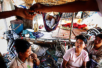 Illegal immigrants from Myanmar pass the time in their humble shelter at a rubbish dump site near Mae Sot December 22, 2009. Despite terrible living condition and the fear from being sent back to their country, several hundred illegal immigrants from Myanmar live and earn an average of one US dollar per day collecting plastic at the rubbish dump near the border town of Mae Sot. Myanmar's long standing political crisis has forced millions of people to cross the border for a better and safer life. The first refugees arrived and set up camps in the Myanmar-Thailand border in 1984. Now, there are over 140,000 refugees in nine official camps along Thailand's western border. Many more are expected to be in unofficial settlements.  REUTERS/Damir Sagolj  (THAILAND)