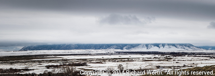 Snow and clouds frame foothills of the Unita range on a springtime afternoon in  southwestern Wyoming.