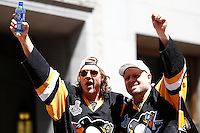 Carl Hagelin #62 of the Pittsburgh Penguins and Phil Kessel #81 of the Pittsburgh Penguins wave to the crowd during the Stanley Cup victory parade in downtown Pittsburgh, Pennsylvania on June 15, 2016. (Photo by Jared Wickerham / DKPS)