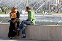 Tripoli, Libya, North Africa - Modern Libyan Women's and Men's Clothing Styles as seen in Public Park near the Green Square, downtown Tripoli.  Man and Woman in Conversation.