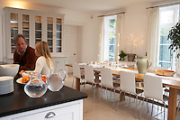 A couple of members of the family in the kitchen/dining room which is furnished with a table decorated for Christmas