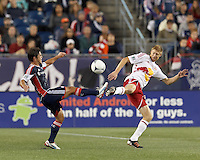 New England Revolution midfielder Ryan Guy (13) and New York Red Bulls defender Markus Holgersson (5) each take a swing at the ball. Despite a red-card man advantage, in a Major League Soccer (MLS) match, the New England Revolution tied New York Red Bulls, 1-1, at Gillette Stadium on September 22, 2012.