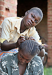 A woman braids the hair of a friend at an agricultural school sponsored by the United Methodist Committee on Relief (UMCOR) in Kaminsamba, Democratic Republic of the Congo. Participants, some of whom stay at the center for several weeks, learn sustainable agricultural practices, animal traction, and beekeeping.