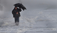 A man walks along the shoreline near Saltcoats as a major winter storm moves in over Scotland..The Met Office issued its highest warning, a red alert..Hundreds of schools have been shut and bridge and road closures are causing disruption. 90mph winds are expected..Parts of England and Northern Ireland are also being hit by extreme wind and rain..Picture: Universal News And Sport (Scotland). 8 December 2011. www.unpixs.com.