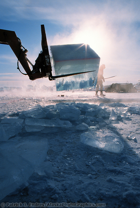 Zoom boom harvests large blocks of ice from a Fairbanks pond. Blocks, cut by chainsaws are used by sculptors in the World Ice Art Championships held each march in Fairbanks, Alaska