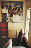 Bulgaria. Province Oblast Lovech. Lukowit. A woman cleans the library's window. An old painting ( winter scene , horses,  crowd, village, boy) is hanged on the wall. © 1997 Didier Ruef
