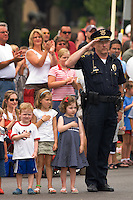 Police officer salutes and his young charges hold their hands over their hearts as the American flag leads the Fourth of July parade.