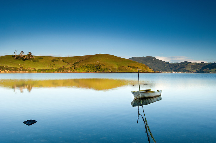 Looking across Otago Harbour from the Otago Peninsula with boat in the foreground. Dunedin, New Zealand - stock photo, canvas, fine art print