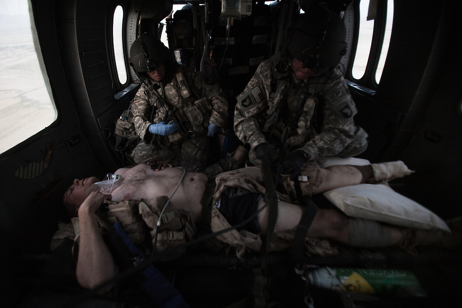 """A flight medic and medical officer work to treated and stabilize a Canadian soldier who has just lost his left foot to an IED strike in western Kandahar province. Scenes from the medical evacuations of wounded Americans, Canadians, and Afghan civilians and soldiers being flown by Charlie Co. 6th Battalion 101st Aviation Regiment of the 101st Airborne Division. Charlie Co. - which flies under the call-sign """"Shadow Dustoff"""" - flies into rush the wounded to medical care out of bases scattered across Oruzgan, Kandahar, and Helmand Provinces in the Afghan south. These images were taken of missions flown out of Kandahar Airfield in Kandahar Province and Camp Dwyer in Helmand Province."""