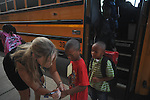 Leslie Waring (left) writes the number of the bus that student Calvin Miller (center) rides on his hand on the first day of school at Bramlett Elementary in Oxford, Miss. on Thursday, August 4, 2011. (AP Photo/Oxford Eagle, Bruce Newman)