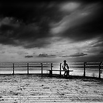 A young boy sits on the end of a pier on an overcast day, lost in thought, looking out to sea.