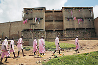 Rwanda. Southern province. District of Muhanga. Central jail of Gitarama. A group of black teenager boys, wearing the pink prisoner's clothes, walk outside of the prison. They are returning to the minors block. Minors in detention. Detention pending trial and after trial, when sentenced to prison. The non-governmental organization (NGO) Fondation DiDé - Dignité en détention runs the Encademi (Encadrement des mineurs) program. Prison centrale de Gitarama. Quartier des mineurs.  © 2007 Didier Ruef