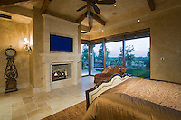 Large luxury bedroom with elegant furniture and fire place and sliding doors that open to outside