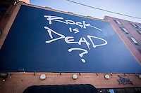 "A huge banner over the John Varvatos store on the Bowery in New York questions whether ""Rock Is Dead"", seen on Tuesday, February 2, 2016. Perversely, the Varvatos store took over the former CBGB location soon after the music venue closed in 2006. The banner appears to be a promotion for the brands Fall/Winter 2016 line for Men's Fashion Week.  (© Richard B. Levine)"