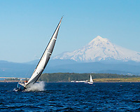 Sailboat with wave splashing on the Columbia River during summer with Mt Hood in the background during blue sky day.  This photo is also on the cover of the Vancouver USA 2011 Visitors Guide.