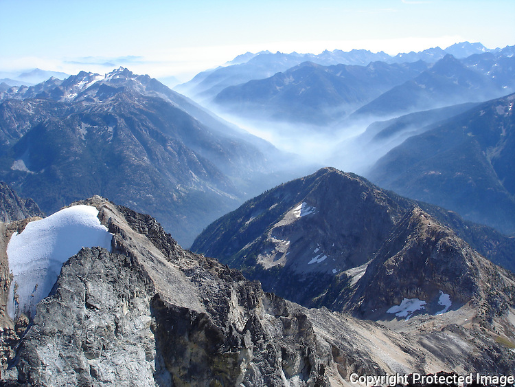 Smoke from a forest fire fills the Stehekin valley below Mount Goode, North Cascades, Washington.