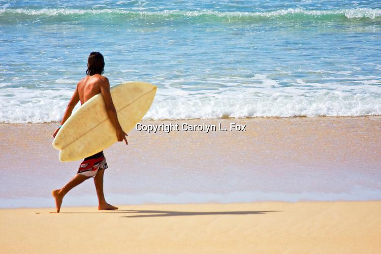 A man walks on the beach carrying a surfboard.