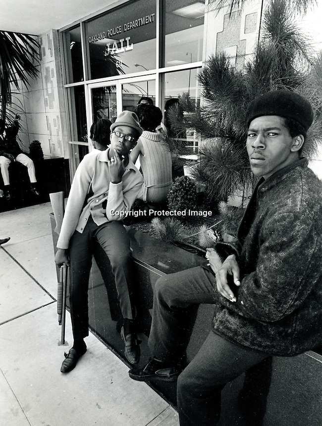 Black Panthers Bobby Hutton (center with shotgun) and a unidentified Panther in front of the Oakland Police Dept. Jail. 1967 photo. (copyright 1967 Ron Riesterer)