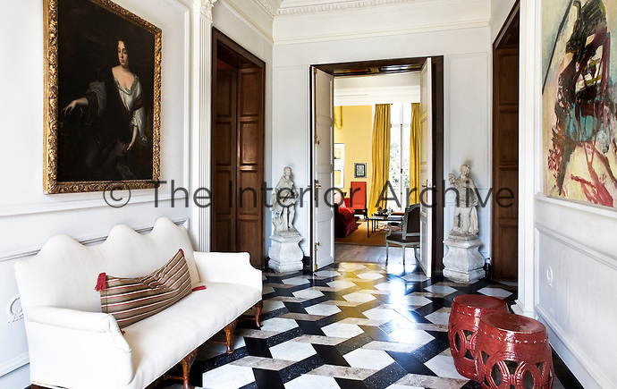 Two contrasting paintings hang on either side of the tiled, stately entrance hall of this country house, combining early modern swagger with contemporary eccentric bravado