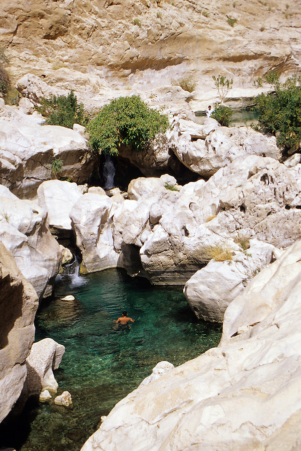 Wadi Bani Khalid, Oman, Arabian Peninsula, Middle East - Rock barriers create natural pools offering hikers an opportunity for a swim in mountain spring water in Oman's coastal mountains.