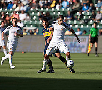 Defender Omar Gonzalez (4) moves past a Boca Junior defender during the second half of a friendly between LA Galaxy and Boca Juniors. The game was held at the Home Depot Center in Carson, CA on May 23, 2010. The final score was LA Galaxy 1, Boca Juniors 0.