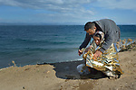 A Syrian refugee wraps insulating material around his mother after arriving on the beach near Molyvos, on the Greek island of Lesbos, on October 31, 2015. They crossed the Aegean in a small, overloaded boat, and local and international volunteers provided them with water, food, and dry clothing. The refugees will then proceed to register with the Greek police and then continue on their way toward western Europe. The boat to Greece was provided by Turkish traffickers to whom the refugees paid huge sums to arrive in Greece.