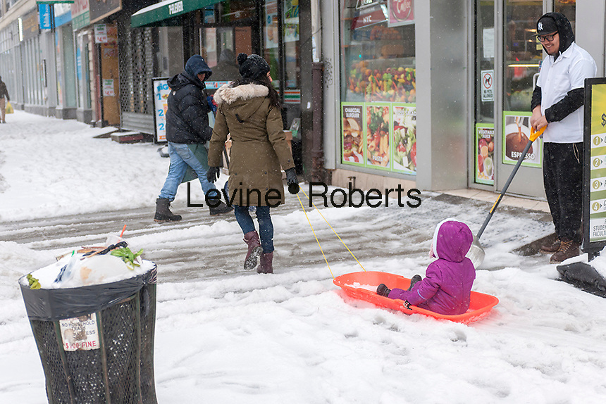 A woman drags a child through the snow on a sled in the Chelsea neighborhood of New York on Tuesday, March 14, 2017. Originally predicted as a blizzard with up to 20 inches of snow the storm has changed its course and only 4 to 6 inches of snow, sleet and rain are expected, accompanied by howling winds of course. (© Richard B. Levine)