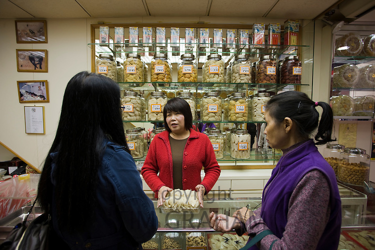 Women buying Chinese herbs and medicines in shop in Wing Lok Street, Sheung Wan, Hong Kong, China