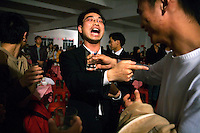 A factory executive argues with a textile worker about who should drink the rice spirit during a Chinese New Year party.